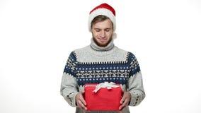 Hombre caucásico joven a cámara lenta que da el regalo de la Navidad de la sorpresa a la cámara metrajes