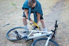 Hombre caucásico joven con las sierras del pelo oscuro la bicicleta que pone en la tierra en parque abandonado con la sierra de m foto de archivo libre de regalías