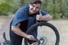 Hombre caucásico joven con los trabajos del pelo oscuro con destornillador con la bicicleta que pone en la tierra en parque aband foto de archivo
