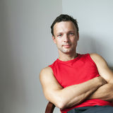Hombre caucásico joven en camisa deportiva roja imagen de archivo