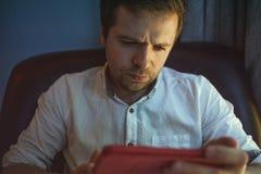 Hombre caucásico joven en el ordenador portátil con el reflejo de luz de la pantalla a la cara que trabaja en casa Imagen de archivo libre de regalías