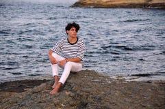 Hombre caucásico joven en la roca en el mar Fotos de archivo