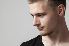 Hombre caucásico joven pensativo aislado en gris Fotos de archivo