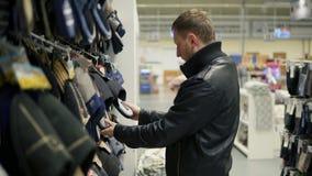 Hombre caucásico joven que elige los deslizadores en el supermercado Selección de homewear cómodo metrajes