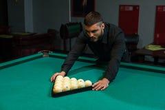 Hombre caucásico joven que juega al juego del billar en club Imagen de archivo