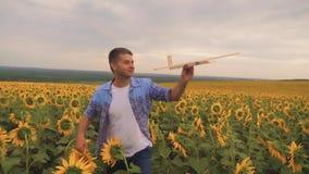 Hombre caucásico joven que juega con el aeroplano de madera en campo del girasol en puesta del sol Cámara lenta almacen de video