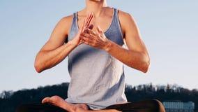 Hombre caucásico joven que se relaja practicando ejercicio de la aptitud de la yoga en la playa cerca del río tranquilo con la ci almacen de metraje de vídeo