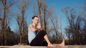 Hombre caucásico joven que se relaja practicando ejercicio de la aptitud de la yoga en la playa cerca del río tranquilo con la ci metrajes