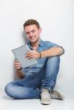 Hombre caucásico joven que se sienta en el piso que sostiene una PC de la tableta Imagenes de archivo