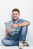 Hombre caucásico joven que se sienta en el piso que sostiene una PC de la tableta Foto de archivo