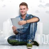 Hombre caucásico joven que se sienta en el piso que sostiene una PC de la tableta MU Imagen de archivo libre de regalías