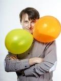 Hombre caucásico joven que sostiene los balones de aire amarillos en su mano Imagen de archivo libre de regalías