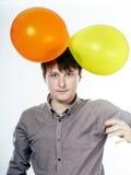 Hombre caucásico joven que sostiene los balones de aire amarillos en su mano Fotografía de archivo libre de regalías