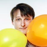 Hombre caucásico joven que sostiene los balones de aire amarillos en su mano Imágenes de archivo libres de regalías