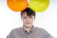 Hombre caucásico joven que sostiene los balones de aire amarillos en su mano Imagen de archivo
