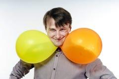 Hombre caucásico joven que sostiene los balones de aire amarillos en su mano Fotografía de archivo