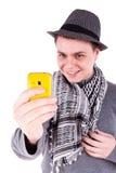 Hombre caucásico joven que toma la foto con un teléfono amarillo Foto de archivo libre de regalías