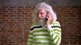 Hombre caucásico mayor de diversión con el pelo blanco y la barba pesada, colgando en su teléfono y hablando con la cara sonrient almacen de metraje de vídeo