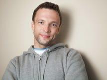Hombre caucásico positivo joven en chaqueta gris Fotos de archivo
