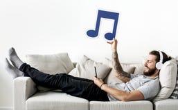 Hombre caucásico que disfruta de la música en casa que lleva a cabo ocio de la nota musical y concepto de la música Fotos de archivo libres de regalías