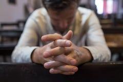 Hombre caucásico que ruega en iglesia Él tiene problemas y pide a dios ayuda fotografía de archivo libre de regalías