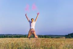 Hombre caucásico que salta en campo durante festival del holi imágenes de archivo libres de regalías