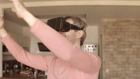 Hombre caucásico que se divierte usando sus auriculares del teléfono móvil VR en casa Máscara de la realidad virtual en la acción almacen de metraje de vídeo
