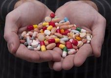 Hombre caucásico que sostiene un manojo de píldoras y de cápsulas imágenes de archivo libres de regalías