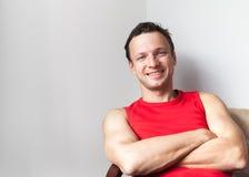 Hombre caucásico sonriente que se sienta con los brazos cruzados imagen de archivo