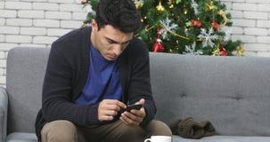 Hombre caucásico usando smartphone en el sofá almacen de metraje de vídeo