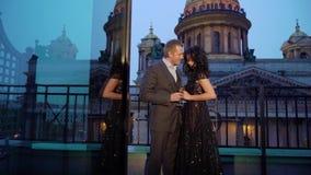 Hombre caucasican joven en traje y mujer morena atractiva en el vestido de lujo negro que permanece en el balcón en una ciudad almacen de metraje de vídeo