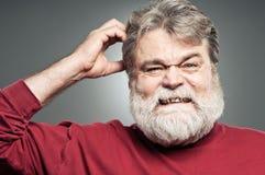 Hombre caucásico maduro que rasguña su cabeza como él olvidó Somethin Imagen de archivo libre de regalías