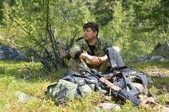 Hombre, cazador, sentándose cerca del rifle y de la mochila en el taiga Foto de archivo