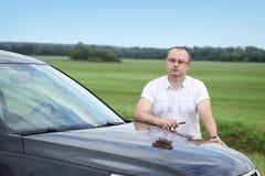 Hombre cerca del coche en el camino Imagen de archivo