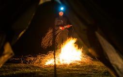 Hombre cerca del fuego del campo en la noche Foto de archivo