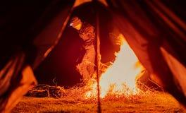 Hombre cerca del fuego y de la tienda del campo Fotos de archivo libres de regalías