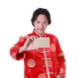 Hombre chino asiático que sostiene el papel de la tarjeta a mano, Año Nuevo chino encendido Imagenes de archivo