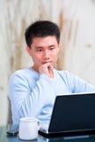 Hombre chino joven que piensa delante de su computadora portátil Fotos de archivo libres de regalías