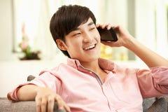 Hombre chino joven que usa el teléfono móvil Imágenes de archivo libres de regalías