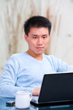 Hombre chino joven que usa la computadora portátil Fotografía de archivo