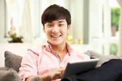 Hombre chino joven que usa la tablilla de Digitaces Fotografía de archivo
