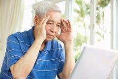 Hombre chino mayor preocupante que usa la computadora portátil en el país Foto de archivo libre de regalías