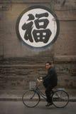 Hombre chino que monta una bici Foto de archivo libre de regalías