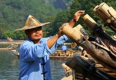 Hombre chino que prepara las balsas de bambú para viajar en el río de nueve curvas imagenes de archivo