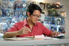 Hombre chino que trabaja en la tienda de informática que comprueba cuentas y facturas Foto de archivo libre de regalías