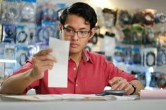 Hombre chino que trabaja en la tienda de informática que lleva a cabo cuentas y facturas Fotos de archivo libres de regalías