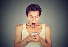 Hombre chocado ansioso que mira el teléfono que ve las fotos de las malas noticias Imagenes de archivo