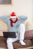 Hombre chocado con el ordenador portátil en un sofá Hombre de negocios con el sombrero de santa Foto de archivo