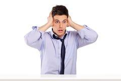 Hombre chocado con incredulidad que se sienta en una tabla Foto de archivo libre de regalías