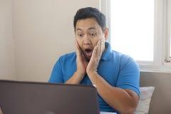 Hombre chocado con la boca abierta para ver malas noticias en Internet foto de archivo